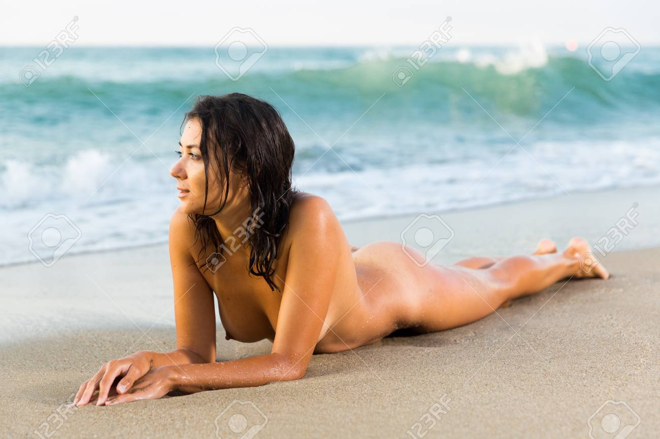 Girls bent over naked in sand